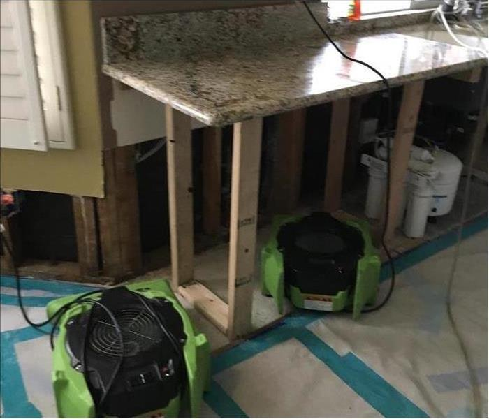 Air movers placed underneath kitchen counter to dry up water damage caused by a broken pipe