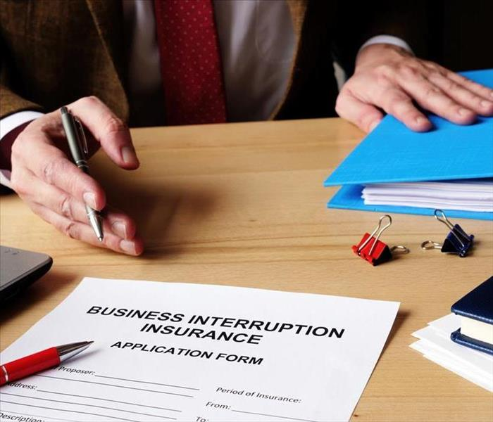 Business insurance application form on a desk, the hand of a person holding a pen.