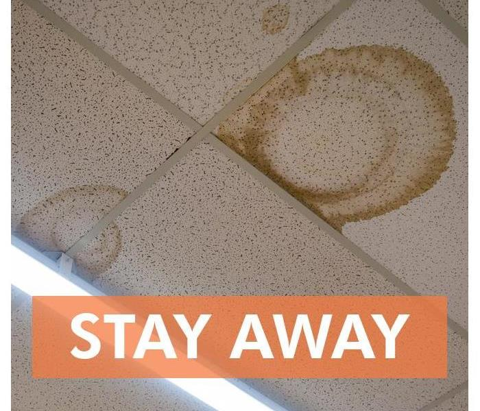 Ceiling tiles damaged with the words STAY AWAY