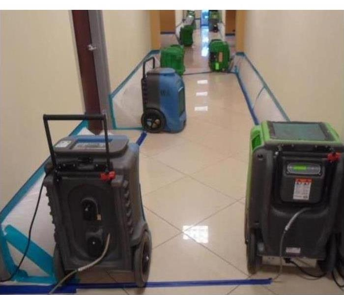 drying equipment in a commercial building, plastic barriers placed on baseboards of wall in order to dry the inside of drywal
